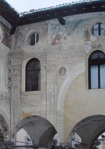 Piazza Ducale di Vigevano - Facciata rivolta a sud - L'impresa del morso sforzesco  dipinta a finto rilievo sull'aggetto del fregio sopra i capitelli.